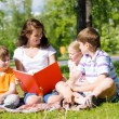 Teacher reads a book to children in a summer park — Stock Photo #27772295