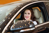 Young woman in the new car in the showroom — Stock Photo