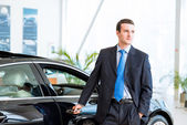 Dealer stands near a new car in the showroom — Stock Photo