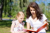 Girl and a young woman reading a book together — Stock Photo