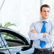 Dealer stands near a new car in the showroom — Stock Photo #28610369