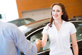 Woman shaking hands with car salesman — Stock Photo