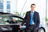 Distribuidor está parado cerca de un coche nuevo en el showroom — Foto de Stock