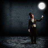 Magician keeps the moon on a string — Stock Photo