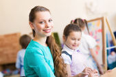 Children with the teacher engaged in painting — Стоковое фото