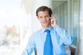 Young businessman talking on cell phone — Stock Photo