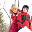 Boy and girl playing with snow in winter park — Stok fotoğraf
