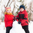 Boy and girl playing with snow in winter park — Stock fotografie