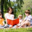 Teacher reads book to children in summer park — Stock Photo #30131687