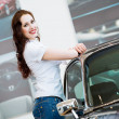 Young woman standing near a car — Stock Photo