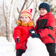 Boy and girl playing with snow in winter park — Stock Photo
