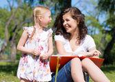 女孩和一个年轻女子在一起读一本书 — 图库照片