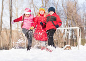 Boy and girls playing with snow in winter park — Stock Photo