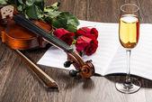 Vidro de violino, rosa, champanhe e música livros — Fotografia Stock
