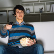 Young man watching television with popcorn — Stok fotoğraf