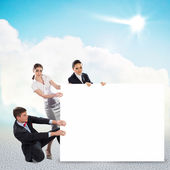 Small group of people holding a blank banner — Stock Photo