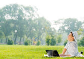Young man working in the park with a laptop — Stock Photo
