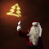 Santa holding a light symbol of Christmas Tree — Stock Photo