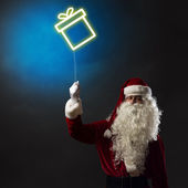 Santa holding a light symbol of the Christmas box — Stock Photo