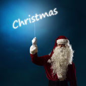 Santa Claus holding a light christmas word — Stock Photo
