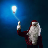 Santa Claus holding a light bulb — Stock Photo