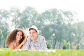 Couple lying on the grass in the summer park — Stok fotoğraf