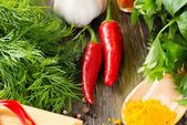 Chilli, herbs and spices lie on a wooden surface — Stock Photo