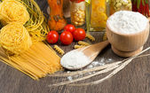 Pasta, tomatoes and flour — Stock Photo