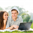 Couple lying together in a park with laptop — Stock fotografie