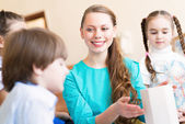 Children with the teacher engaged in painting — Stock Photo