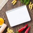 Spices and vegetables around notebook — Stock Photo
