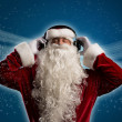 Stock Photo: SantClaus is listening to music