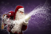 Santa Claus blows magic sparks — Stock Photo