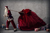 Santa Claus pulls a huge bag of gifts — Stock Photo