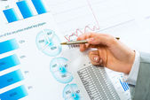 Female hand pointing pen on financial charts — Stock Photo