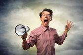 Young man shouting using megaphone — Foto Stock
