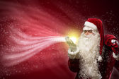 Santa Claus blows with hands magic sparks — Stock Photo