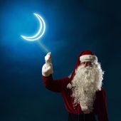 Santa Claus holding a light symbol of the moon — Stock Photo