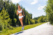 Young athletic woman running on the road — Foto de Stock