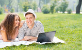 Couple lying together in a park with laptop — Foto Stock