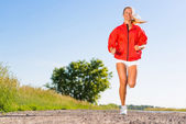 Young athletic woman running on the road — Stok fotoğraf