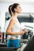 Attraktiv ung kvinna springa på ett löpband — Stockfoto