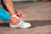 Young woman tying shoelaces on sneakers — Stock Photo