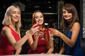 Three girls raised their glasses in a nightclub — Stock Photo