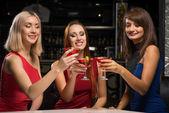 Three girls raised their glasses in a nightclub — Stock Photo