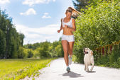 Young athletic woman running on the road — Stockfoto