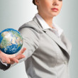 Businesswoman holds up an Earth — Stock Photo
