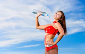 Sport girl with a bottle of water — Stockfoto