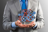 Business man holds up a mechanism of gears — Stockfoto