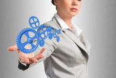 Business woman holds up a mechanism of gears — Stock Photo